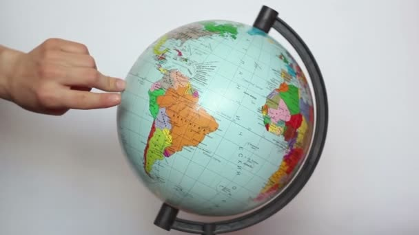 A female, hand with fingers steps on the earth globe. Beautiful female fingers walk around the globe, symbolizing a trip around the world.