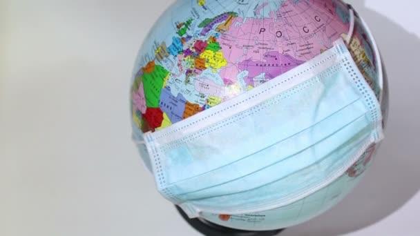 Earth globe wears a medical mask. A medical mask is worn on an earth globe. World quarantine, coronavirus pandemic.