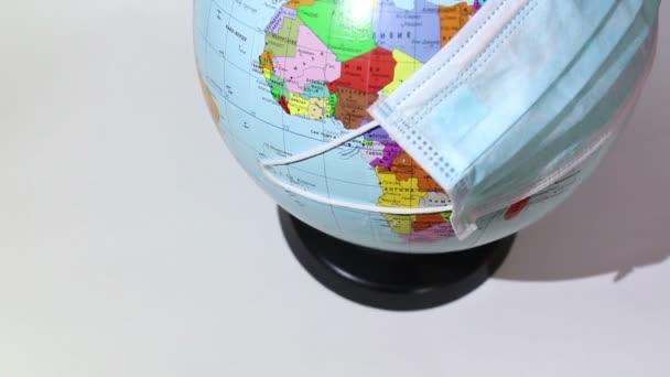 Earth globe wears a medical mask. A medical mask is worn on an earth globe. World quarantine, coronavirus pandemic. World quarantine symbol.