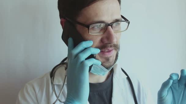 Ein junger, gut aussehender Arzt mit Brille und medizinischer Gesichtsmaske berät am Telefon. Ein junger Arzt berät einen Patienten während der Quarantäne telefonisch.
