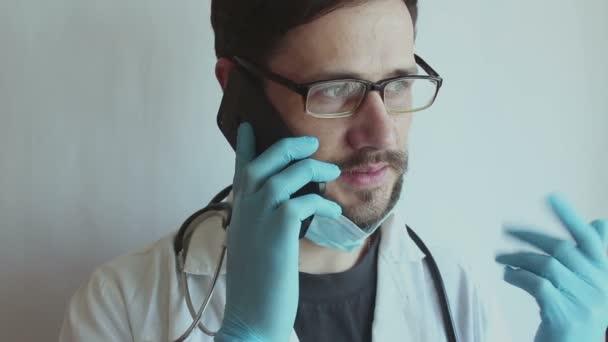 Ein junger gutaussehender Arzt mit Brille und medizinischer Gesichtsmaske berät am Telefon.