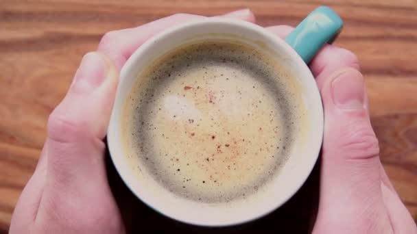 Mužské ruce drží šálek aromatické kávy. Na dřevěném stole stojí šálek aromatické kávy. Muž si ohřeje ruce šálkem kávy. Oživující káva s lahodnou mléčnou pěnou.