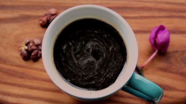 Šálek aromatické kávy stojí na dřevěném stole.