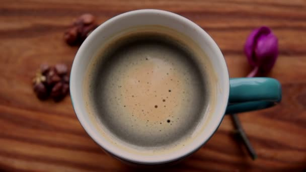 Female hands hold a cup with aromatic coffee. A cup of aromatic coffee stands on a wooden table. Aromatic coffee with foam. Invigorating coffee with delicious milk foam.