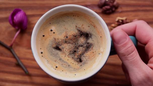 Ženské ruce drží šálek s aromatickou kávou. Na dřevěném stole stojí šálek aromatické kávy. Oživující káva s lahodnou mléčnou pěnou.