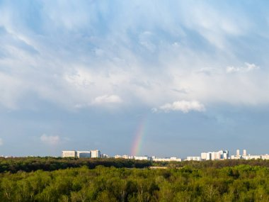 blue rainy clouds and rainbow over city on sunny spring day
