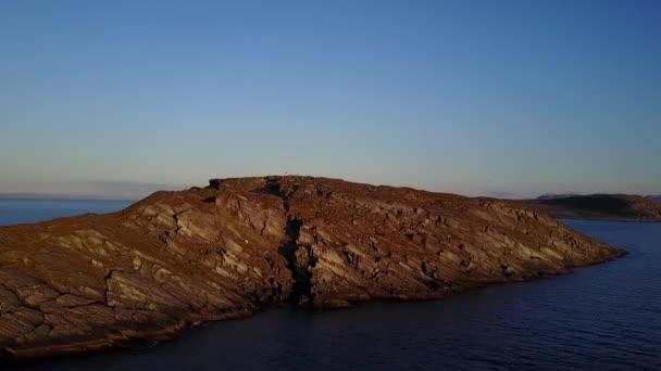 Půlnoční slunce osvětluje fjord. Z dronu letícího na mys. Maják je viditelný na okraji útesu.