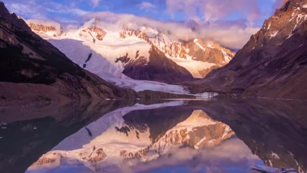 Time lapse of a colorful sunrise with moving clouds at a lake or lagoon with mount Torre on the background, on a summer sunny day with mountains and a glacier, near campsite De Agostini, El Chalten, Santa Cruz, Patagonia Argentina