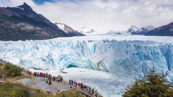 Time lapse of moving clouds on a sunny day in Perito Moreno glacier, with people walking at the view point and the ice breaking and falling into the cold waters. El Calafate, Santa Cruz, Argentina