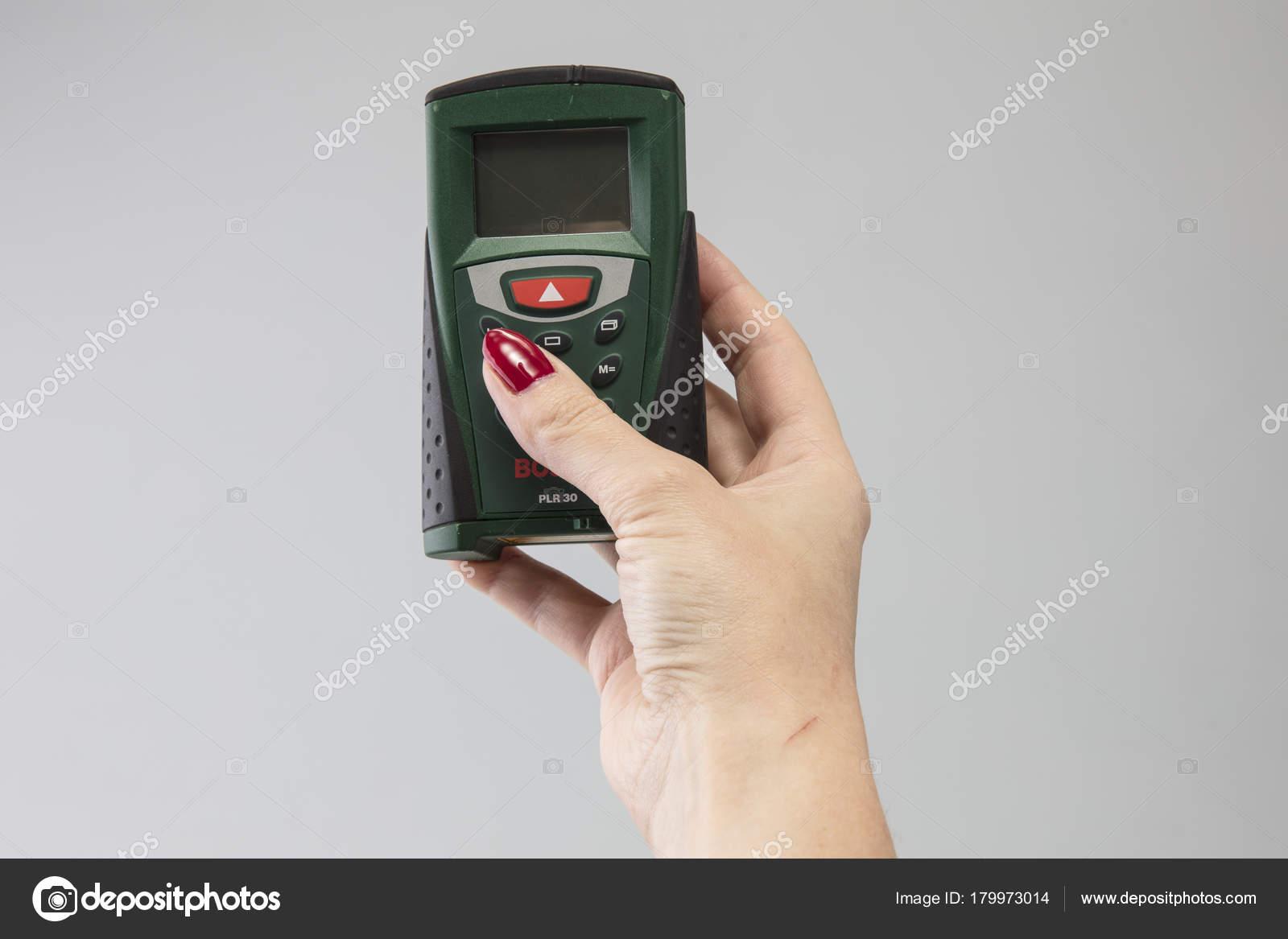 Laser entfernungsmesser der hand einer frau u redaktionelles