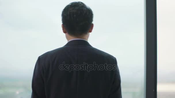 asian businessman looking around thinking in office