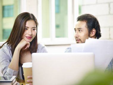 young asian coworkers working together in office using laptop co