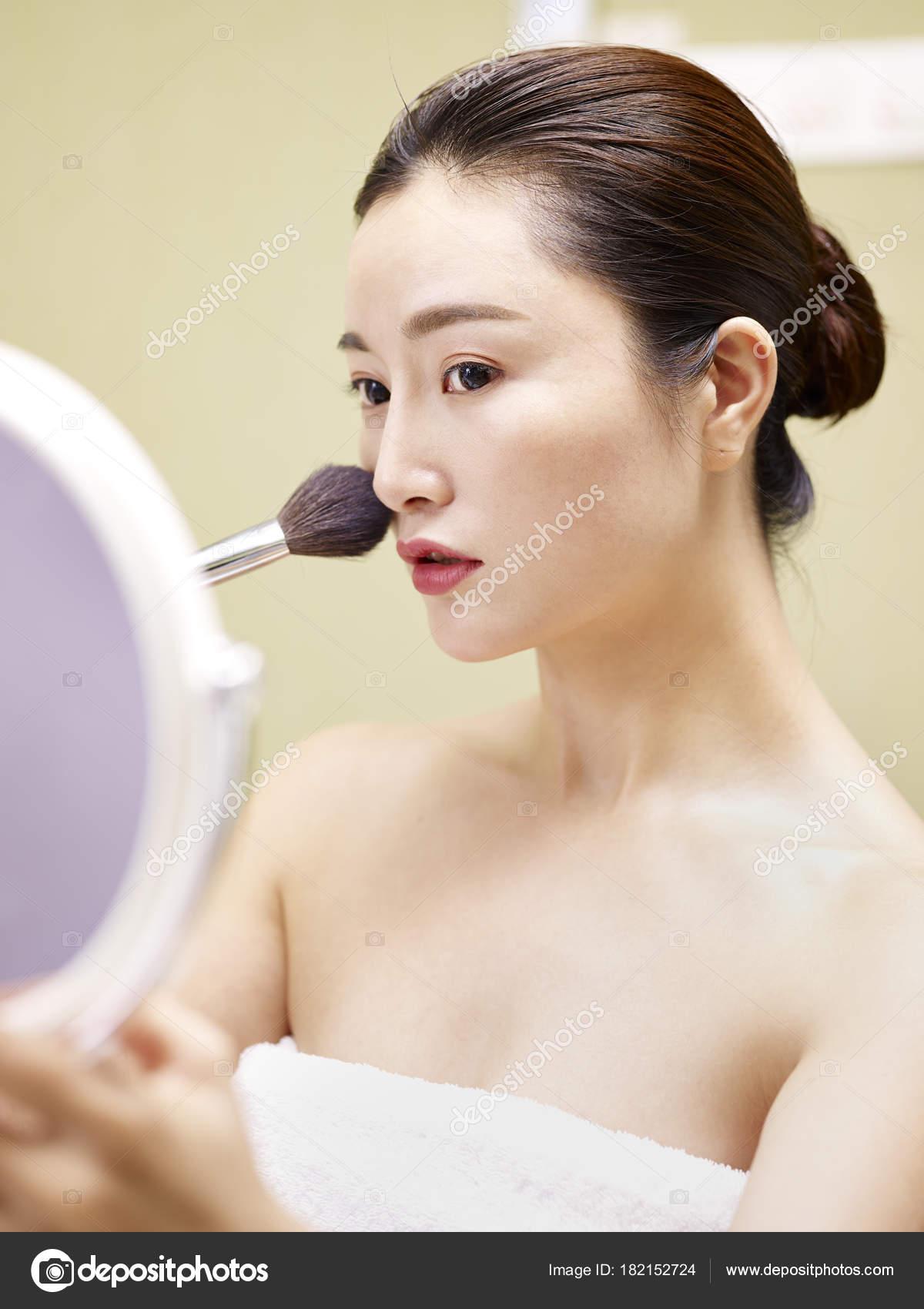 mujer asiática joven mirando en el espejo mientras se aplica ...