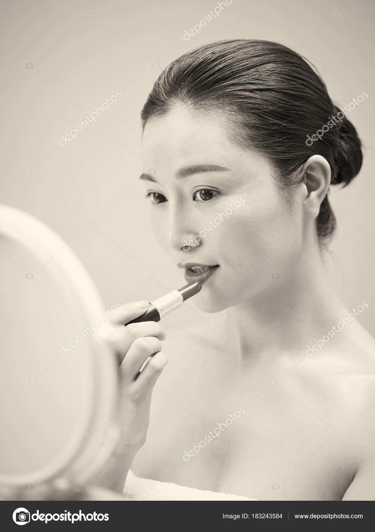 mujer asiática joven mirando en el espejo mientras se aplica el ...