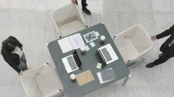 three corporate executives in modern company arriving at meeting table to discuss business plan in office, high angle view