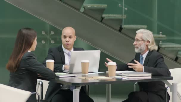 multiethnic corporate executives discussing business in meeting in office using laptop computer.