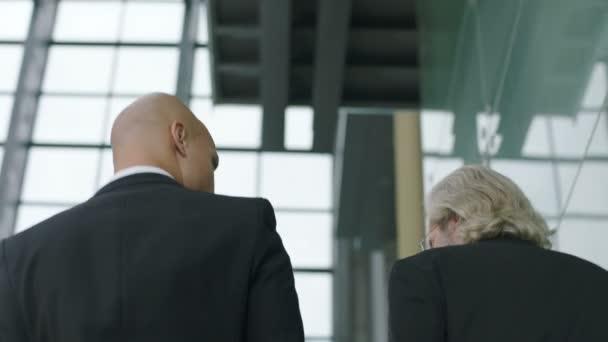 dvou vedoucích pracovníků mluví diskutovat podnikání zatímco vzestupně schody v společnosti