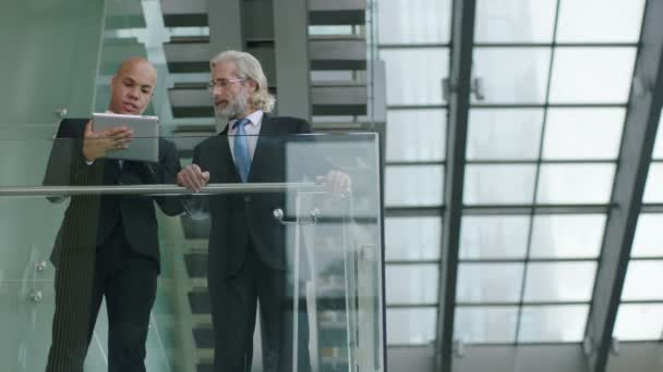 two corporate executives standing on second floor on a glass and steel building discussing business using digital tablet.