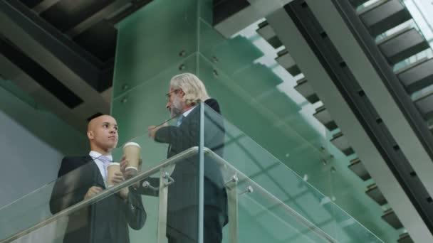 Zwei Firmenchefs stehen im zweiten Stock und diskutieren über Geschäfte.