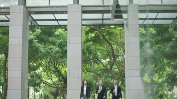 white collar corporate executives with coffee or bag in hand chatting while walking to work in modern building.