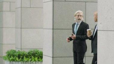 two business men holding coffee and handbag walking talking entering modern building.