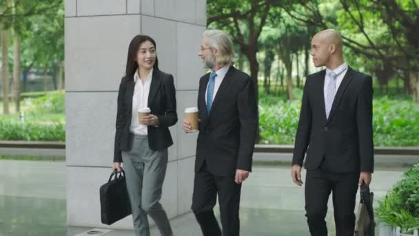 multiethnic corporate executives with coffee and computer bag arriving at modern building.