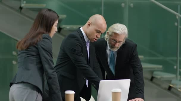 three corporate executives meeting in company office discussing business using laptop computer.