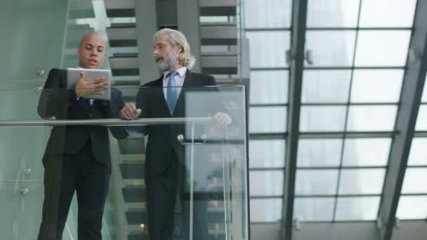 two corporate executives standing on second floor of a glass and steel building discussing business using digital tablet.