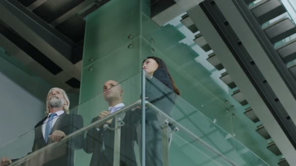three corporate executives standing on second floor of modern glass building discussing architectural project