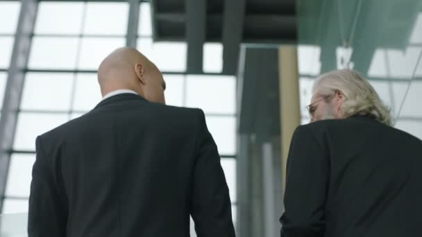 rear view of two corporate executives chatting while ascending stairs in company.