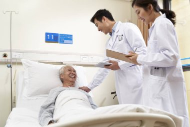 two young asian doctors talking old man at bedside