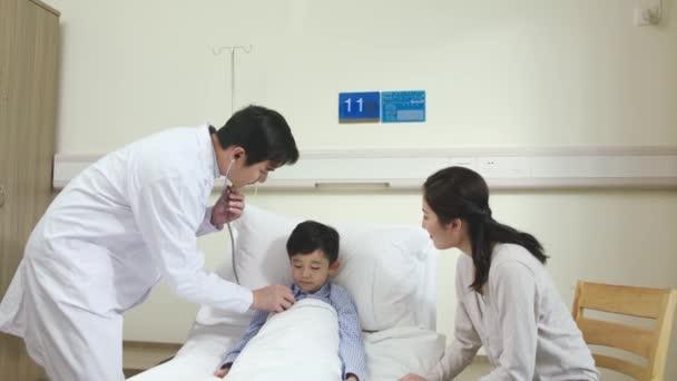 junge asiatische männliche Arzt macht Runden Untersuchung und Gespräch mit Kind Patient und Mutter im Krankenhaus Station