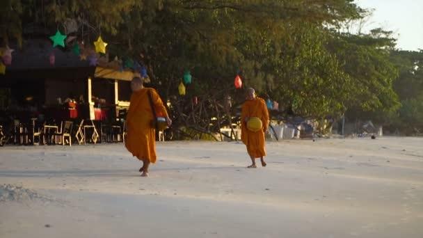 zwei thailändische Mönche in orangefarbenen Roben am Strand spazieren, während sie Almschalen tragen