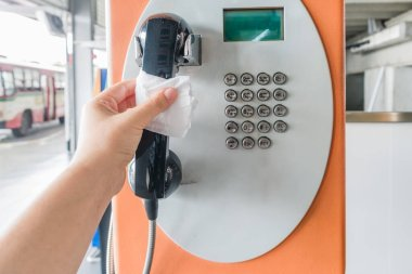Asian hand holding local public telephone in Thailand through a napkin, risk to contaminated with germs virus bacteria and pathogen. Covid-19 disease coronavirus outbreak concept