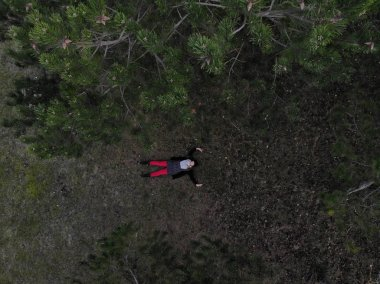 Top View of a Female with red pants Lying in a Forest during win