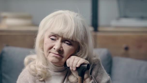 Ideges idős nő demenciával, egyedül ül a kanapén.