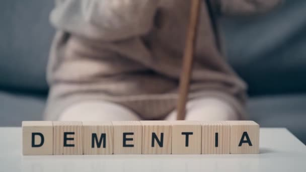 Cubes with dementia word and senior woman on sofa