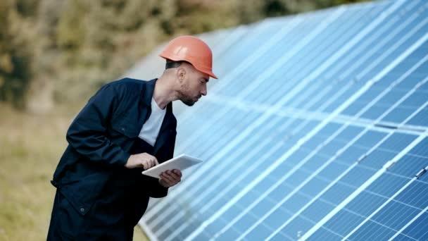 Ingenieur mit Gadget und Blick auf Solarmodul