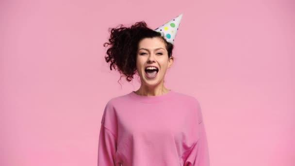 glückliche Frau bläst in Party-Gebläse isoliert auf rosa