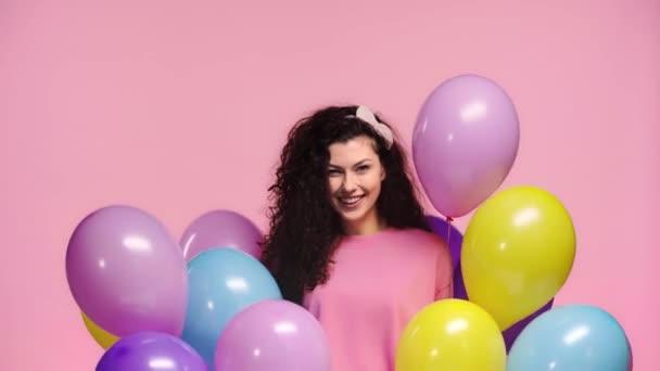šťastná dívka drží balónky izolované na růžové