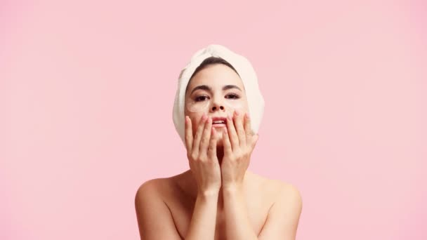 smiling naked girl with towel on head and eye patches massaging face isolated on pink