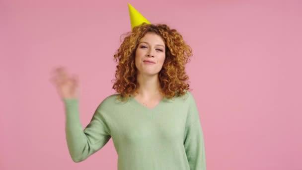 boldog nő integetett kezét és fújja party kürt elszigetelt rózsaszín