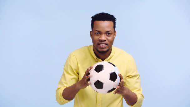 boldog afro-amerikai férfi néz labdarúgó játék elszigetelt kék