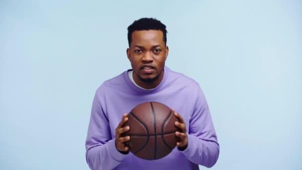 šťastný africký Američan sleduje basketbal hry izolované na modré
