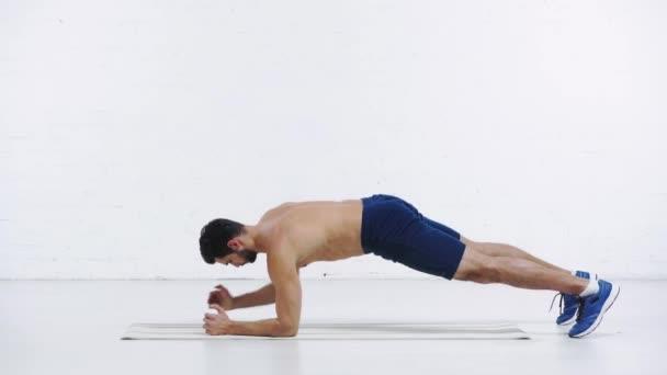 sportovec dělá nízké prkno na bílém pozadí