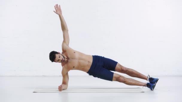 sportovec dělá boční prkno na bílém pozadí