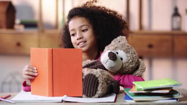 mosolygós afro-amerikai gyermek olvasás könyv Teddy maci