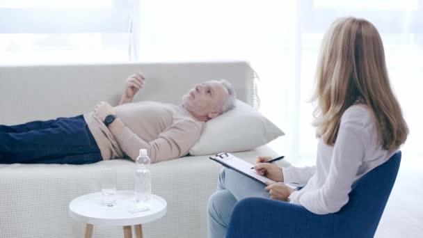 Reifer Mann liegt auf Couch und spricht mit Psychologe und schreibt auf Klemmbrett