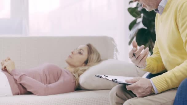 cropped view of psychologist talking to patient lying on couch