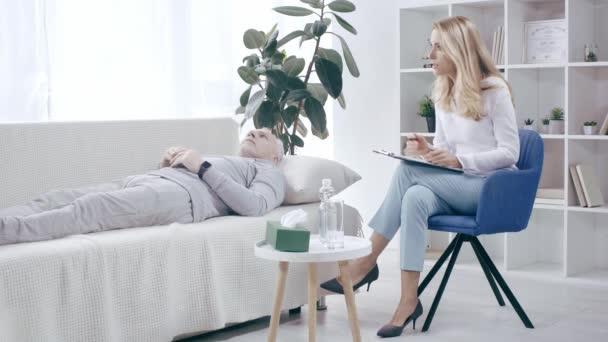 Reifer Sportler liegt auf Couch und spricht mit Psychologe